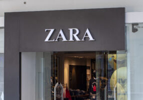 Manila, the Philippines - 22 March 2018: Zara brand name on store entrance in SM Mall of Asia shopping mall. Fashion store label. Casual wear shop. Famous retail company. Men and women clothes brand